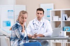 Hoestende vrouw bezoekende arts bij kliniek stock fotografie