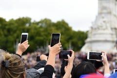 Hoeveelheid mobiele die telefooncamera's wordt opgeheven om het veranderen van de wacht te filmen en te fotograferen stock fotografie