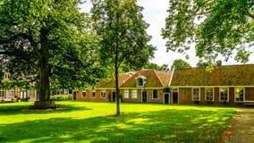 Hof mit Gras und alte Eiche und Kastanienbäume im historischen Dorf von Midden Beemster Lizenzfreie Stockbilder