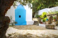 Hof vor traditioneller griechischer kleiner orthodoxer Kapelle, Garten und Brunnen Agio Nikolaos Kreta, Griechenland stockfotos