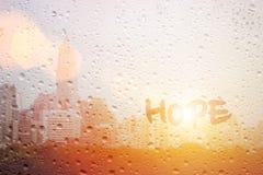 Hoffnung des abgehobenen Betrages auf Fenster stockbild