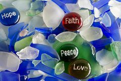 Hoffnung, Glaube, Frieden und Liebe auf Glassteinen mit Seeglas Stockfotografie
