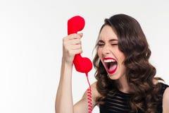 Hoffnungslose betonte Frau mit Retro- Frisur schreiend im Telefonhörer Stockfoto