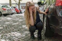 Hoffnungslose Frau, die den Schaden ihres Autos überprüft stockbild