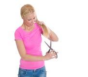 Hoffnungslose Frau schneidet ihr schädigendes blondes Haar Lizenzfreies Stockbild