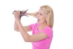 Hoffnungslose Frau schneidet ihr schädigendes blondes lokalisiertes Haar - Stockfotografie