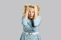 Hoffnungslose reife Frau auf grauem Hintergrund Lizenzfreies Stockfoto