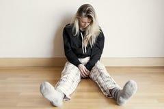 Hoffnungslose und traurige Frau, die auf Boden sitzt Stockbilder