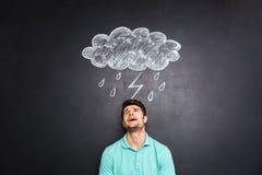 Hoffnungsloser deprimierter Mann, der unter dem Regen gezeichnet auf Tafelhintergrund schreit Lizenzfreie Stockbilder