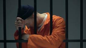 Hoffnungsloser eingesperrter Mann, der auf den Stangen, glaubend deprimierte, psychologische Hilfe sich lehnt stock video