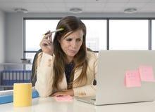 Hoffnungsloser Geschäftsfrauleidendruck am Laptopcomputertisch, der gesorgt schaut Stockbild