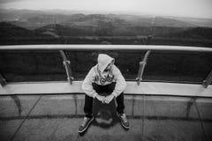 Hoffnungsloser Jugendlicher, der in den Bergen sitzt Stockfoto