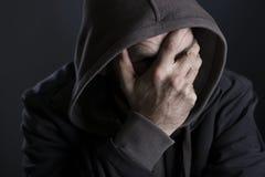 Hoffnungsloser Mann, der Leid und die Schmerz zeigend facepalming ist Lizenzfreie Stockfotografie