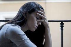 Hoffnungsloser trauriger lateinischer schauender Balkon der Frau zu Hause verheerende und niedergedrückte leidende Krise stockfotos