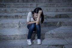 Hoffnungsloses und deprimiertes Sitzen der schönen und traurigen hispanischen Frau auf städtischem Stadtstraßentreppenhaus Stockbilder