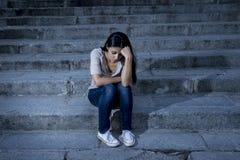 Hoffnungsloses und deprimiertes Sitzen der schönen und traurigen hispanischen Frau auf städtischem Stadtstraßentreppenhaus Stockfotos