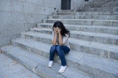 Hoffnungsloses und deprimiertes Sitzen der schönen und traurigen hispanischen Frau auf städtischem Stadtstraßentreppenhaus Stockfotografie