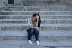 Hoffnungsloses und deprimiertes Sitzen der schönen und traurigen hispanischen Frau auf städtischem Stadtstraßentreppenhaus Stockbild
