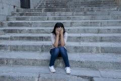 Hoffnungsloses und deprimiertes Sitzen der schönen und traurigen hispanischen Frau auf städtischem Stadtstraßentreppenhaus Lizenzfreies Stockbild