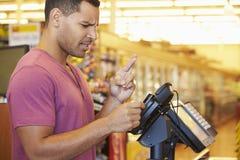 Hoffnungsvoller Kunde, der für den Einkauf an der Prüfung mit Karten-Kreuz zahlt Stockfotos