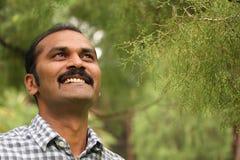 Hoffnungsvolles, entspanntes u. glückliches asiatisches/indisches Mannlächeln Lizenzfreies Stockfoto
