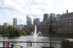 The hofvijver pool with fountain along the parliament building and the skyline of the hague.  royalty free stock images
