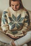 Hogar acogedor La muchacha hermosa está leyendo un libro en la cama buena mañana con té Chica joven bonita que se relaja El conce foto de archivo