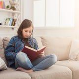 Hogar acogedor Muchacha pensativa joven con el libro Imágenes de archivo libres de regalías