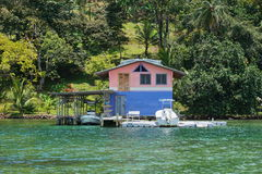 Hogar costero con el muelle y la casa barco sobre el agua Fotografía de archivo libre de regalías