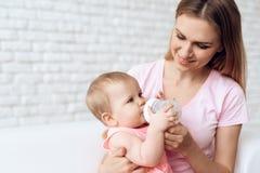 Hogar de alimentación sonriente de la botella de leche del bebé de la madre fotografía de archivo libre de regalías