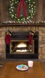 Hogar de la chimenea de la Navidad con las galletas y la leche para Papá Noel fotos de archivo