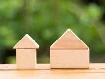 Hogar de madera grande y pequeño hogar de madera en piso con el fondo verde Préstamo hipotecario o concepto casero del edificio Imagenes de archivo