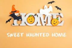 Hogar decorativo de la palabra de Halloween en fondo amarillo fotografía de archivo