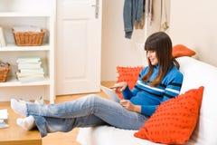 Hogar del adolescente con el ordenador de la tablilla de la pantalla táctil Foto de archivo libre de regalías
