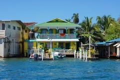 Hogar del Caribe de la costa con los barcos en el muelle Fotografía de archivo