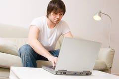 Hogar del hombre joven con la computadora portátil Foto de archivo