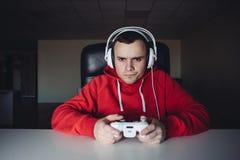 Hogar del hombre joven y los juegos el jugar en la palanca de mando El videojugador juega a los juegos de ordenador usando un gam foto de archivo libre de regalías