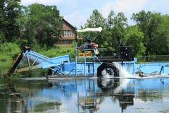 Hogar del lago con la máquina segador de la vegetación Imagen de archivo libre de regalías
