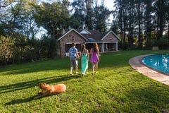 Hogar del perro del muchacho de las muchachas que camina Foto de archivo libre de regalías