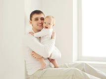 Hogar joven sonriente feliz del padre y del bebé en el sitio blanco cerca de la ventana Imagen de archivo libre de regalías
