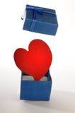 Hogar rojo que abre una caja de regalo azul Imágenes de archivo libres de regalías