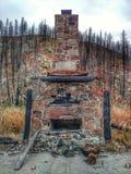 Hogar y chimenea de piedra después de un incendio fuera de control foto de archivo