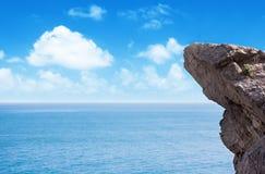 Hoge bergklip bij de kalme overzeese en hemelachtergrond Stock Afbeeldingen