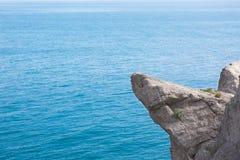 Hoge bergklip bij de overzeese achtergrond Stock Foto