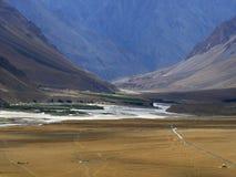 Hoge bergvallei, in de voorgrond een reusachtige gele woestijn met een draad van de weg, op de achtergrond een rivier onder steil Royalty-vrije Stock Afbeeldingen