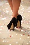Hoge die hielen bij enkels met confettien worden gekruist stock foto