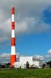Hoge fabrieksschoorsteen op blauwe hemel Royalty-vrije Stock Afbeeldingen