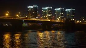 Hoge gebouwen van woonwijk, auto's op de nachtbrug stock video