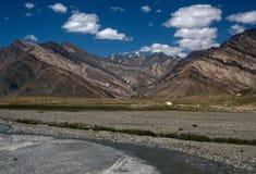 Hoge gestreepte bruine bergen de vallei van de rivier, in voorgrondboog het aquamarijn zuivere water, Zanskar, Tibet, India Stock Foto