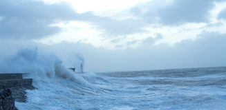 Hoge golven die een licht huis raken stock afbeeldingen